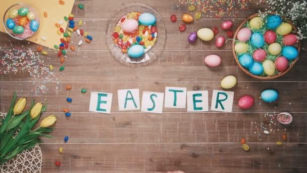 Mann stellt Wort Ostern am Tisch mit Ostereiern dekoriert. Ansicht von oben