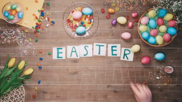 Mann stellt Wörter Ostern Verkauf auf Tisch mit Ostereiern dekoriert. Ansicht von oben