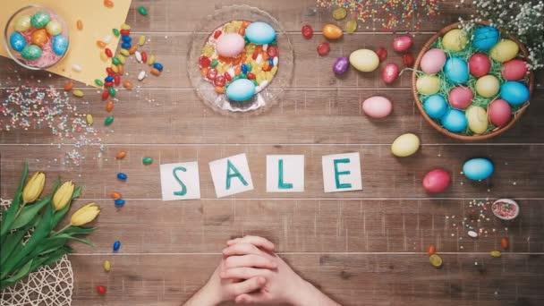 Mann stellt Wort Verkauf auf Tisch mit Ostereiern dekoriert. Ansicht von oben