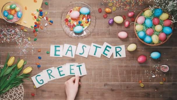 Mann stellt Wörter Ostern Bandbreiten auf Tisch mit Ostereiern dekoriert. Ansicht von oben