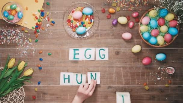 Mann legt Worte Eiersuche auf Tisch mit Ostereiern dekoriert. Ansicht von oben