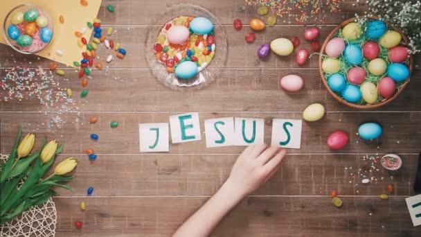 Mann stellt Wort Jesus am Tisch mit Ostereiern dekoriert. Ansicht von oben