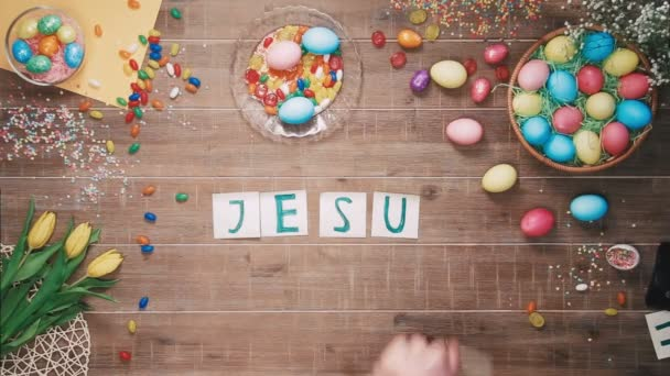 Mann stellt die Worte Jesus liebt U auf Tisch mit Ostereiern dekoriert. Ansicht von oben