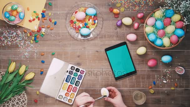 Muž Malování velikonoční vajíčko a digitální tablet s zelenou obrazovkou leží na stole zdobí velikonoční vajíčka pohled shora