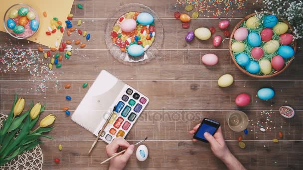 Man painting easter egg and using smartphone on table decorated with easter eggs. Top view