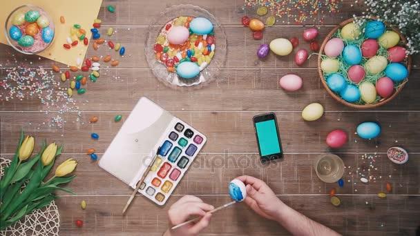 Mann-Malerei-Osterei und smart Phone mit Greenscreen liegt auf Tisch mit Ostereiern dekoriert. Ansicht von oben