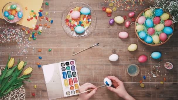 Mans ruce malování kraslic na stole zdobí velikonoční vajíčka. Pohled shora