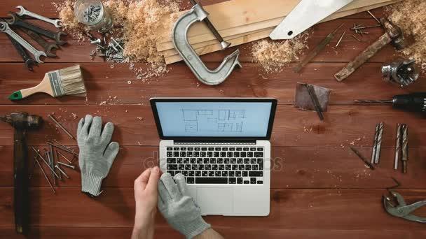 Pohled shora řemeslník ruce pomocí přenosného počítače při pohledu na práci na projektu
