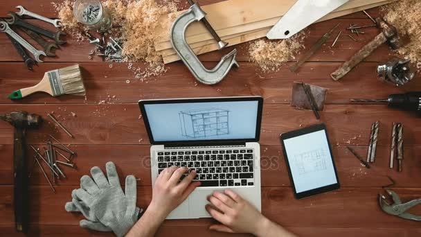 Pohled shora řemeslník ruce pomocí přenosného počítače a digitální tabletu při pohledu na skicách se plán prostorového uspořádání