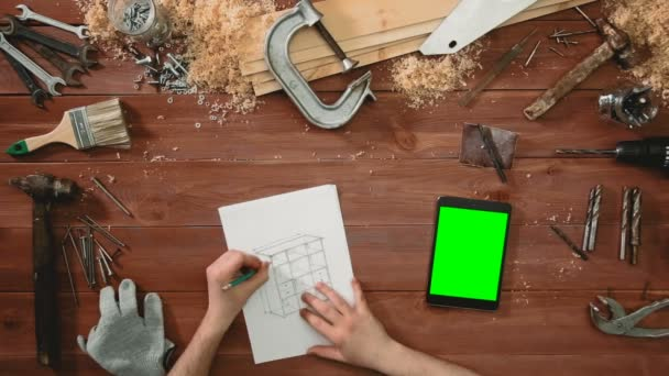 Top view craftsman hands drawing a sketch of cabinet, digital tablet green screen lying on desk