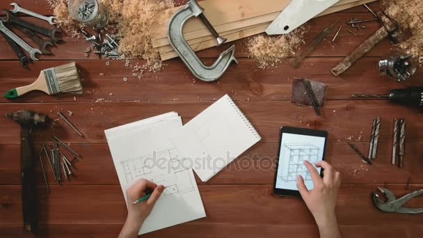 Top view craftsman hands drawing a sketch of floor plan on paper using digital tablet