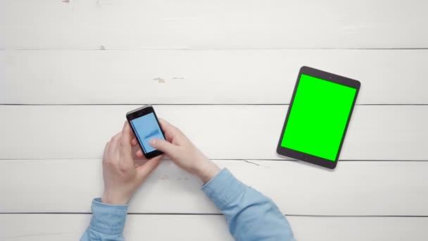Männliche Hände arbeiten mit Big-Data-Diagrammen und Diagrammen auf Smartphone und digitalem Tablet mit grünem Bildschirm, der von oben auf weißem Schreibtisch liegt