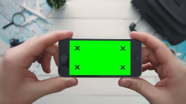 Pohled shora cestující ruka hospodářství telefon horizontální s zeleným plátnem a sledování body na bílý dřevěný psací stůl