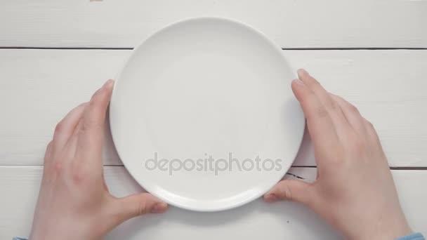 Pohled shora mužské ruce dávat bílý talíř a příbory na bílém stole shůry kopie prostor