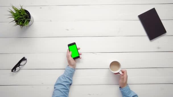 Pohled shora mužské ruce zobrazeno více gesta na smartphone s zelenou obrazovkou na bílý stůl z výšky