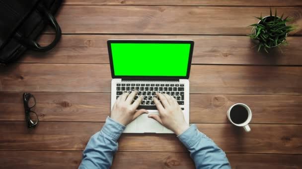 Männliche Hände arbeiten am Laptop mit grünem Bildschirm am weißen Schreibtisch von oben