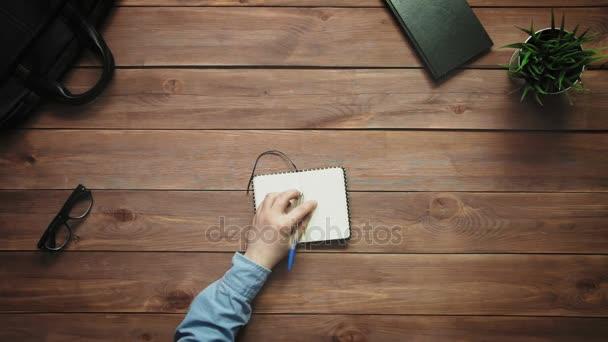 Felülnézet férfi kezét írásban notebook, fehér íróasztal, felülről