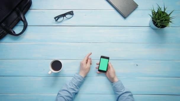 Felülnézet férfi kezét mutatja több gesztusok a smartphone-val zöld képernyő fehér pult fölött