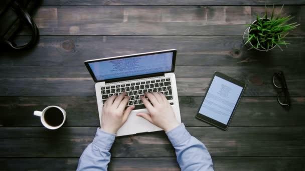 Pohled shora mužské ruce pracují na přenosném počítači a digitální tablet s velkými objemy dat grafy ležící na bílém stole shora
