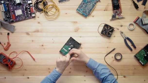 Pohled shora počítačový technik opravy pevného disku na dřevěné desce s nástroji a elektronických součástek