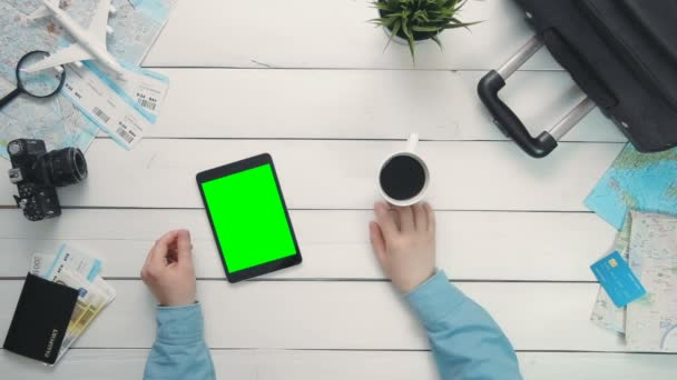 Travelling concept Top view travelers hands showing multiple gestures on digital tablet with green screen at white wooden desk