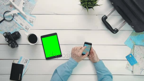 Pohled shora cestující ruce při pohledu na mapu světa pomocí smartphonu a tabletu digitální s zelenou obrazovkou ležící bílý dřevěný psací stůl