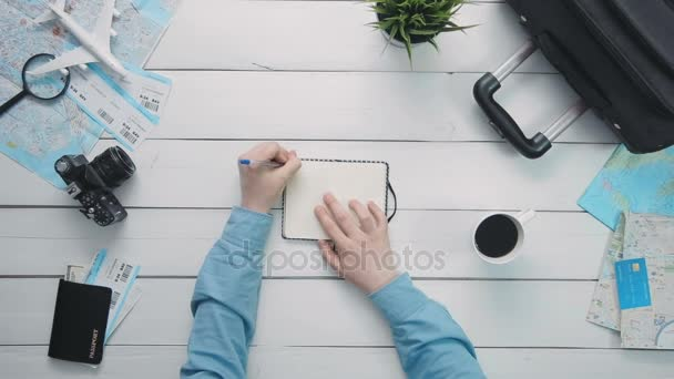Top view travelers hands maing notes in the notebook at white wooden desk