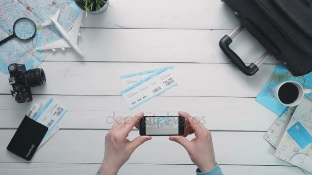 Top view travelers hands taking a picture of airplance tickets with smart phone at white wooden desk