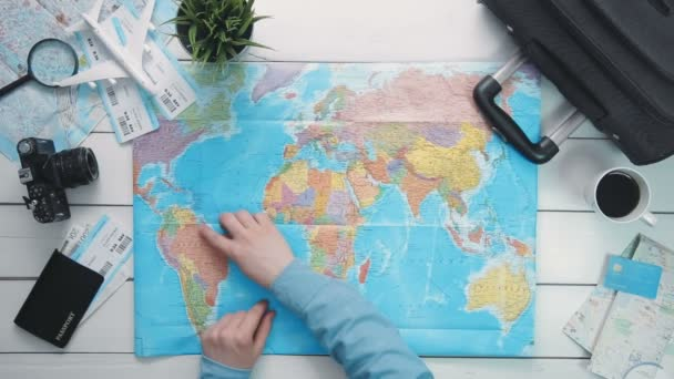 Top view travelers hands picking a country for travelling at white wooden desk