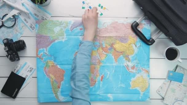 Pohled shora ruční sběr země pro cestování a dát vlajku pin na bílý dřevěný psací stůl