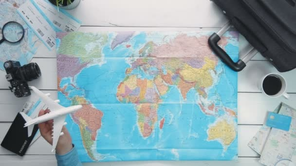 Travelling concept Top view travelers hand flying a toy airplane above the world map at white wooden desk