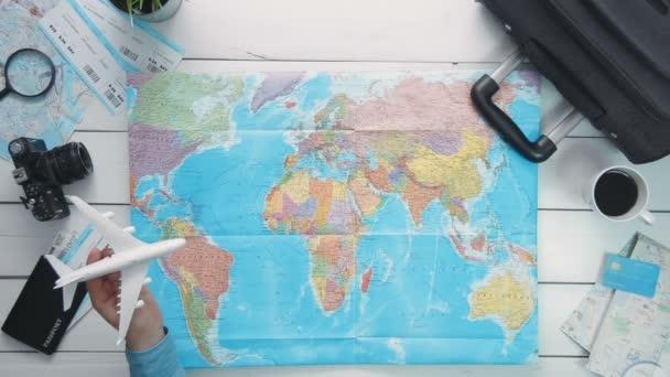 Utazás koncepció felülnézet utazók kezében egy játék repülőgép a világ Térkép fehér fa íróasztal felett repülő