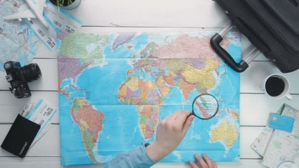 Top view travelers hands looking at world map using magnifying glass at white wooden desk