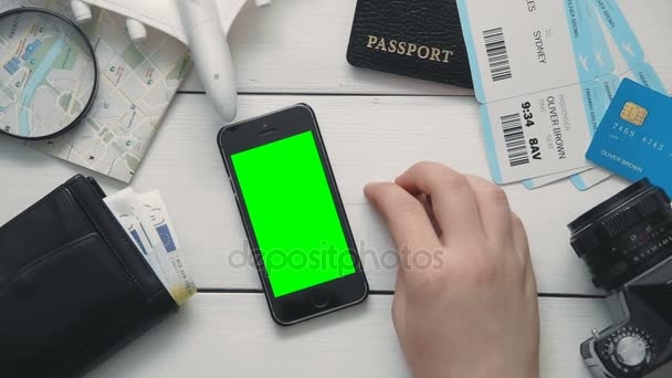 Travelling concept Top view travelers hand showing multiple gestures using smartphone with green screen at white wooden desk