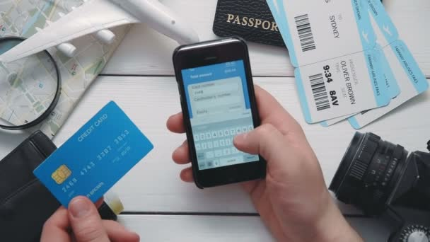 Top view travelers hands paying for airplane tickets on line using smartphone at white wooden desk