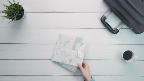Felülnézet idő telik utazók kezében elhelyezés egy lapos feküdt segítségével utazási cikkek, fehér fa íróasztal