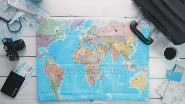 Top view time lapse travelers hands putting pins in the map showng countries he has visited at white wooden desk