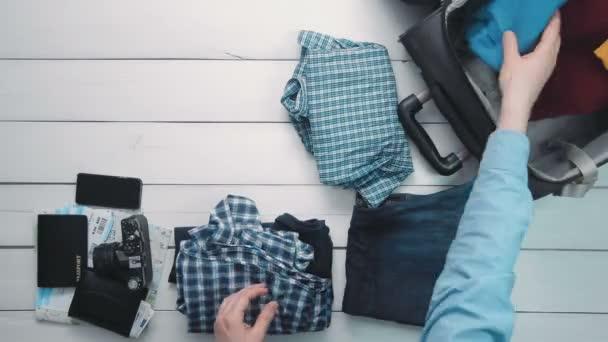 Pohled shora čas zanikla cestující ruce kufřík s oblečením a cestování položky na bílý dřevěný psací stůl