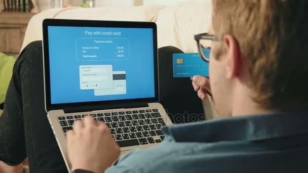 junger Mann füllt Kreditkartennummer auf seinem Laptop aus, um online einzukaufen