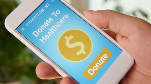 Man making an online donation to healtcare using charity applicaiton on smartphone