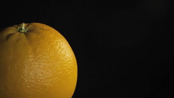 Big juiced orange, macro Spins on dark background
