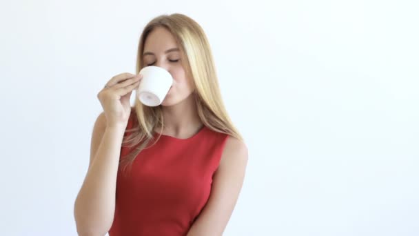 Young pretty girl drinks hot beverage