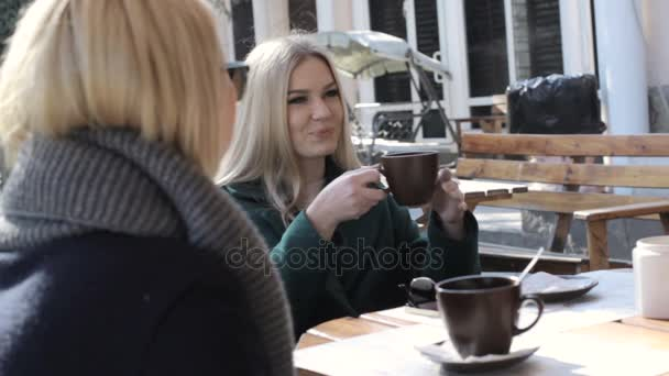 Two attractive young girls sit at an outdoor cafe and talk
