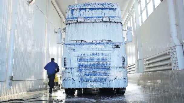 Zaměstnanec čistí auto na mytí aut