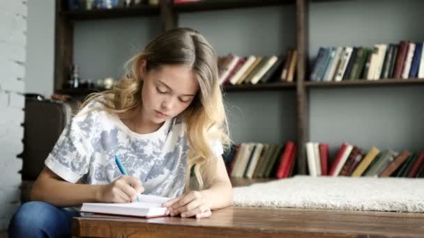 Nagyon tizenéves lány levelet ír a notebook-on iskola Vértes
