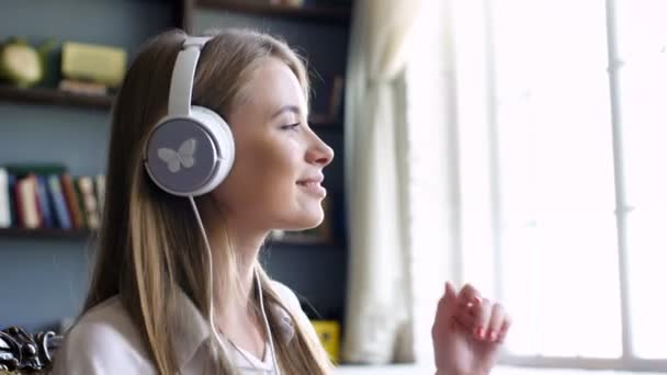 Cute girl with white headphone dances in the room