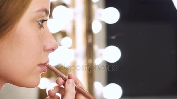 Ragazza sensuale che applica cosmetico con la matita per le labbra