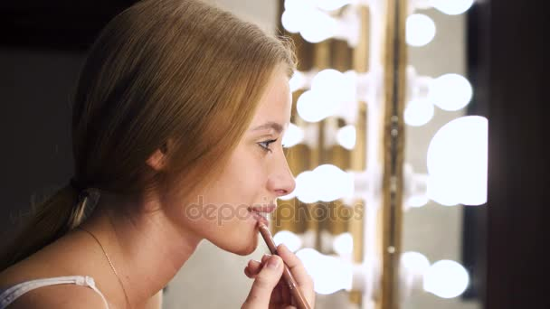 Cool girl applying cosmetic with lip liner