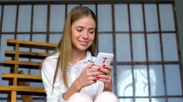 Mladá dívka použití mobil pro procházení sociálních sítí nebo messaging online