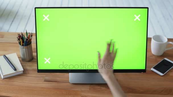 Womans hand using pc with green touch screen monitor